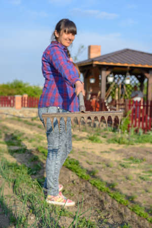 tines: Gardener holding up a large old rusty rake with sharp tines as she works in her vegetable garden in spring, focus to the rake Stock Photo