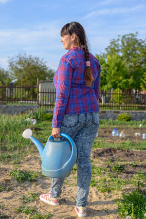 transplanted: Rear view of a an active woman gardening outdoors in a home vegetable garden standing holding a blue plastic watering can