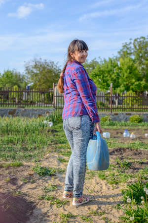 self sufficient: Rear view of a an active woman gardening outdoors in a home vegetable garden standing holding a blue plastic watering can