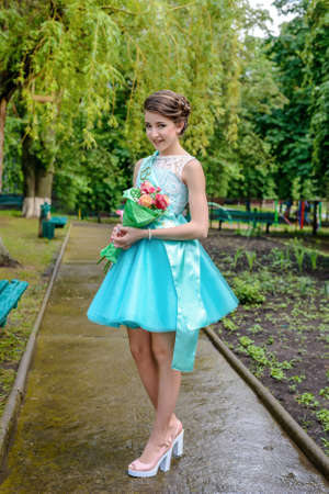 demure: Cute girl in blue beauty pageant dress, ribbon, bouquet and pink high heels outside on sidewalk in park