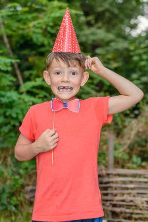 El muchacho joven payaso con los apoyos de cabina de fotos al aire libre en el jardín que lleva un sombrero cónico de color rojo y la celebración de una pajarita mientras se tira de una cara divertida