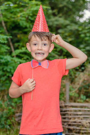 Young boy clowning with photo booth props outdoors in the garden wearing a red conical hat and holding a bow-tie as he pulls a funny face