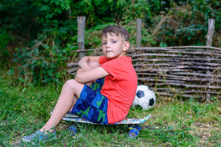 jaunty: Confident jaunty young boy sitting on a skateboard with folded arms outdoors in a rustic garden with his football alongside him