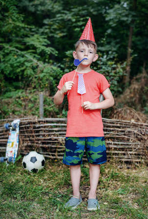pompous: Handsome young boy smoking a bright blue photo booth accessory pipe as he stands outdoors in a rustic garden with a solemn expression wearing a party hat
