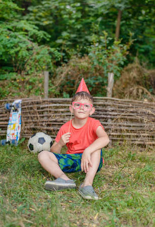 Small boy sitting on the grass in front of an old rustic garden fence playing with photo booth props holding a set of spectacle frames to his eyes Stock Photo