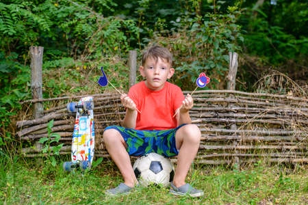 befuddled: Befuddled boy seated on soccer ball in front of compost pile with symbols of smiling face and smoking pipe on sticks outside with colorful skateboard
