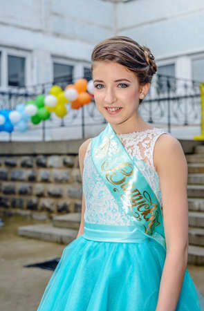 demure: Cute single young girl in blue beauty pageant dress with large ribbon across her top and colorful balloons in background