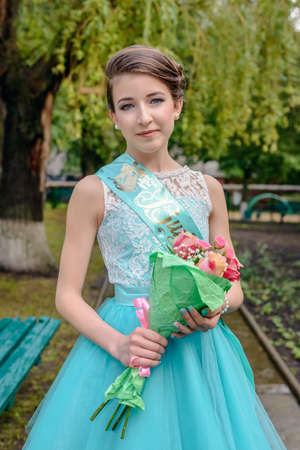 demure: Cute single young girl in blue beauty pageant dress with large ribbon across her top holding flower bouquet