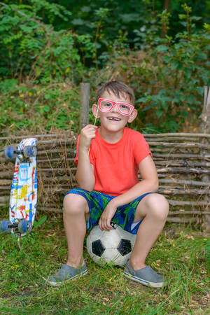 Funny young boy missing a front tooth sitting on his soccer ball grinning and playing with photo booth props holding a pair of glasses to his eyes Stock Photo