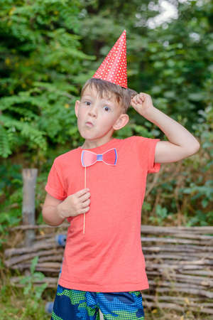 clowning: Young boy clowning with photo booth props outdoors in the garden wearing a red conical hat and holding a bow-tie as he pulls a funny face