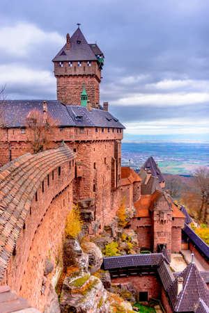 fortified wall: Beautiful red brick European castle with long fortified wall with titled roof overlooking city under partly cloud skies
