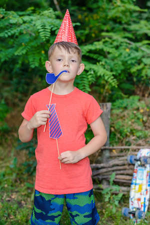 solemn: Handsome young boy smoking a bright blue photo booth accessory pipe as he stands outdoors in a rustic garden with a solemn expression wearing a party hat