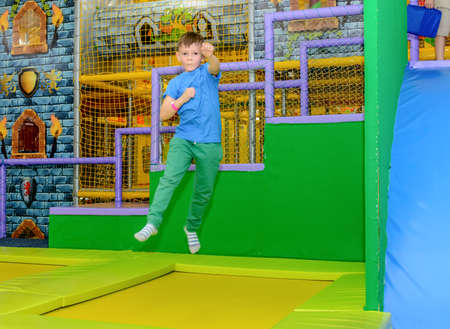 Exuberant young boy bouncing on a trampoline punching at the air with his fists on a colorful kids playground