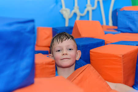 Cute happy little boy crouched down amongst loose colorful red and blue plastic cubes at a funfair or playground grinning at the camera Stock Photo