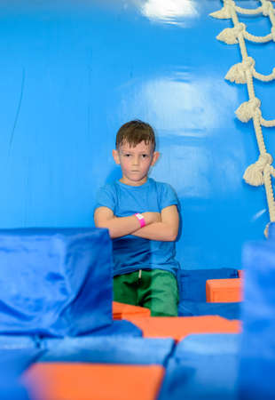 amongst: Cute little boy crouched down amongst loose colorful red and blue plastic cubes at a funfair or playground grinning at the camera