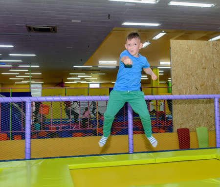jaunty: Happy little boy boy bouncing on a trampoline at an indoor playground punching the air with his fist in excitement Stock Photo