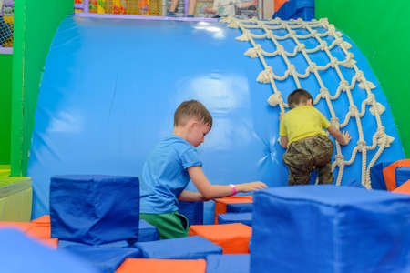 scaling: Two young boys playing in a kids playground with one clambering up a rope net and the other playing with red and blue plastic cubes