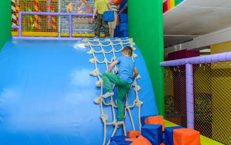 clambering: Two young boys playing in a kids playground with one clambering up a rope net and the other playing with red and blue plastic cubes