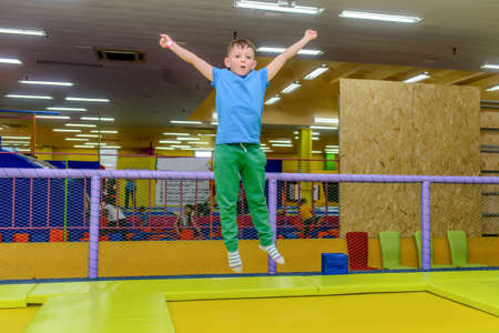 jaunty: Happy little boy bouncing on an indoor trampoline at a funfair or playground with his aims outstretched Stock Photo