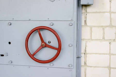 impregnable: Old fashioned reinforced steel vault door with a circular red handle set into a brick wall of a building