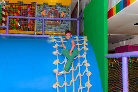 Little boy sliding down a curved plastic blue slide at a kids playground after climbing up to the top on a rope net