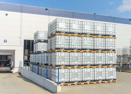 Packed pallets IBC container of retail goods standing outdoors at a large modern warehouse in summer sun