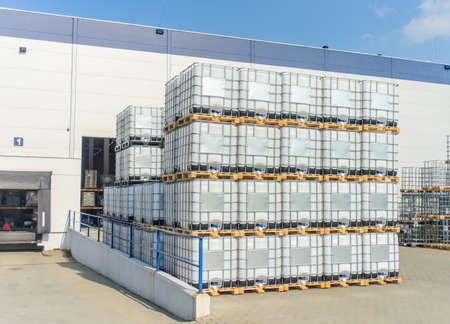 Verpakt pallets IBC container van de retail goederen zich in openlucht bij een groot modern magazijn in de zomerzon