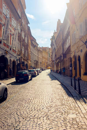 Czech Republic, Prague June 21, 2016:Narrow brick paved street in Prague with sunlight flare pouring over the top of buildings Editorial