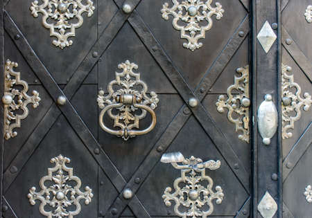 ornate door: Arabesque metal motifs on an ornate door with a geometric diamond pattern over the wood and a ring handle, close up detail Stock Photo