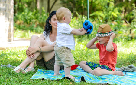 entertaining: Young boy entertaining a toddler making faces while wearing a trendy hat as they play on a rug on a lawn watched by their mother