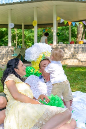 Cute little boy celebrating his first birthday outdoors on a rug in the park with his loving parents and colorful decorations in green , yellow and white