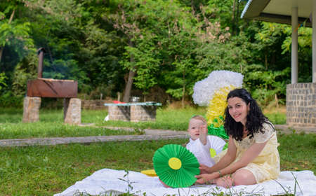 Happy young mother celebrating with her baby sitting on a rug outdoors on the grass in a park below a large number 1 decoration for his first birthday Stock Photo
