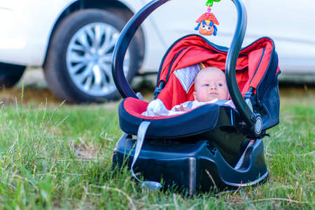 quiet baby: Sweet quiet little baby resting outdoors in a carrycot placed on the grass in the shade of a car watching the camera with a calm expression