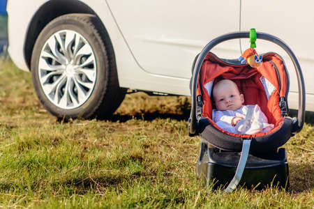 angel alone: Sweet quiet little baby resting outdoors in a carrycot placed on the grass in the shade of a car watching the camera with a calm expression