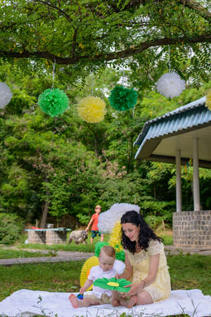 maternal: Happy young mother celebrating with her baby sitting on a rug outdoors on the grass in a park below a large number 1 decoration for his first birthday Stock Photo