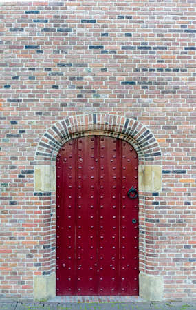 inset: Old medieval red studded wooden door in a brick wall with variegated colors of brick in an architectural background