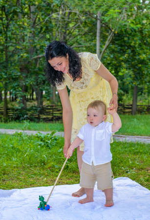 sonaja: Attractive happy smiling young mother with her toddler son playing together with a toy on a white blanket on the grass in a lush green park with trees Foto de archivo