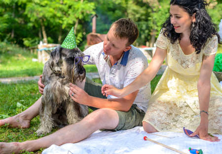 Young couple with a dog in fancy dress wearing a green party hat and photo booth glasses relaxing on a lawn in a lush park on a summer day