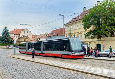 praga: Czech Republic, Praga -28 Jule 2016:Electric street train in European city by edifice rounds the corner of cobblestone avenue