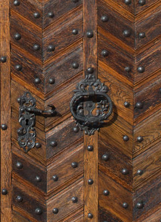 inlay: Old wooden door with decorative inlay in a herringbone pattern and metal studs with focus to an ornate escutcheon with keyhole and ring handle