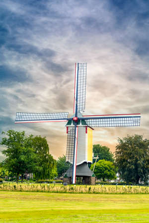 rotational: Colorful wooden windmill with four sails in an agricultural field alongside a highway against a cloudy blue sky