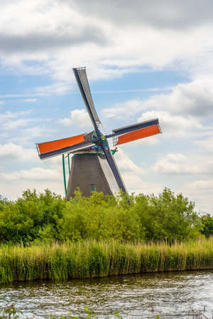 Traditional windmills on farm during summer with green buildings in large field under beautiful skies