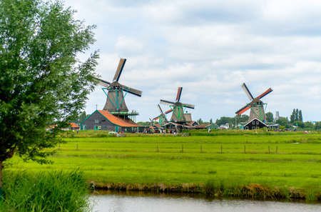 Windmills on the horizon at farm with green grass near canal under windy cloudy skies