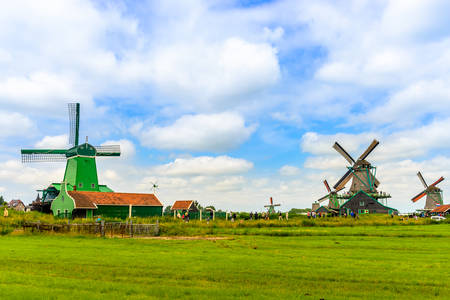 green buildings: Traditional windmills on farm during summer with green buildings in large field under beautiful skies