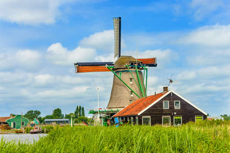 Rear angle view on old windmill over roof building with clay tile roof under scattered clouds Stock Photo