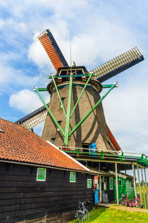 single story: Tall windmill with wide base and painted green supports behind single story farmhouse during summer