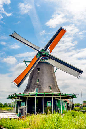 Tall windmill with wide base and painted green supports behind single story farmhouse during summer