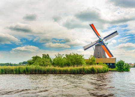 traditional windmill: Old traditional windmill on shoreline with wind blowing grass. Includes copy space.