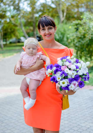 Mother holding a cute baby girl and bouquet of colorful purple and white flowers giving the camera a cheesy grin with a quirky expression