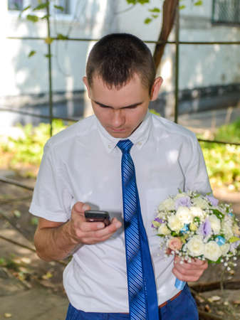 arboles frondosos: Man holding a bouquet of flowers chatting on a mobile phone as he stands outdoors under the shade of leafy trees listening with a serious expression Foto de archivo